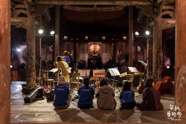 一群今秋志工坐在鹿港龍山寺戲台下